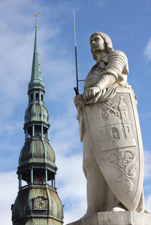 La estatua de Roland y la iglesia de San Pedro en Riga, Letonia foto de archivo