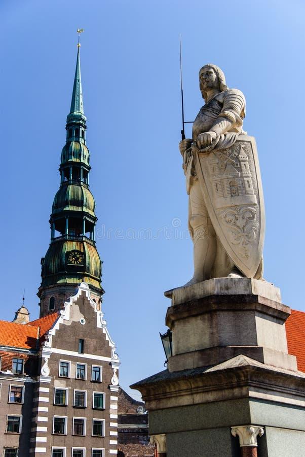 La estatua de Roland y la iglesia de San Pedro, Riga, Letonia imagen de archivo libre de regalías