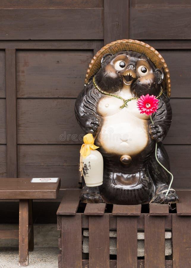 La estatua de Tanuki sostiene la flor roja y el frasco habitual del motivo imágenes de archivo libres de regalías