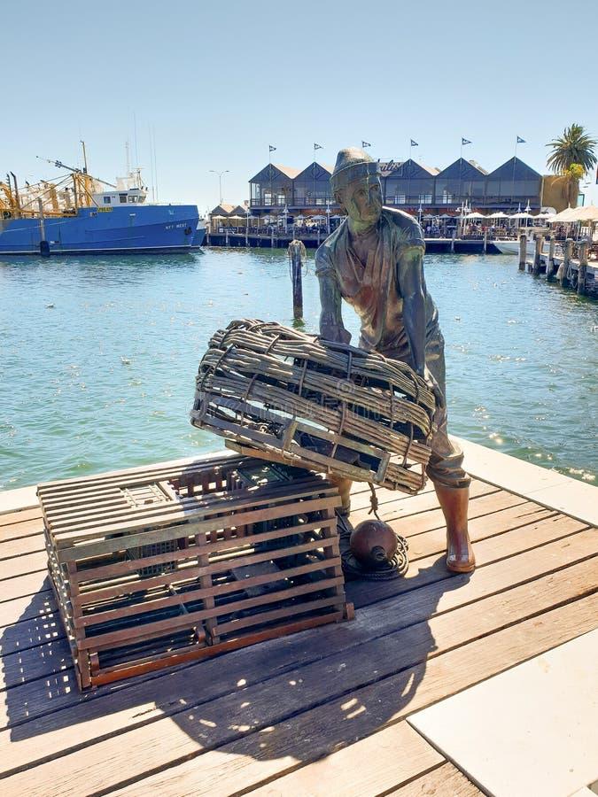 La estatua del embarcadero conmemora al pescador local foto de archivo