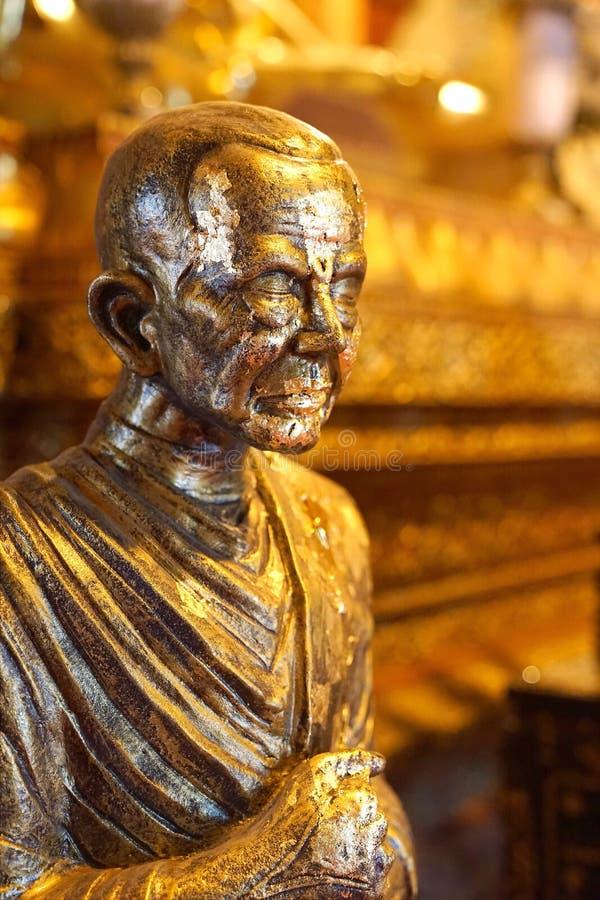 La estatua del monje famoso cubierta por la hoja de oro cubre en el pasillo principal de Wat Phumin o de Phu Min Temple, el templ foto de archivo libre de regalías