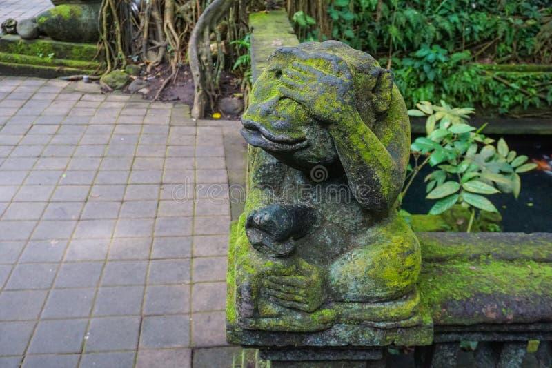 La estatua del mono en Bali cubrió con el musgo foto de archivo