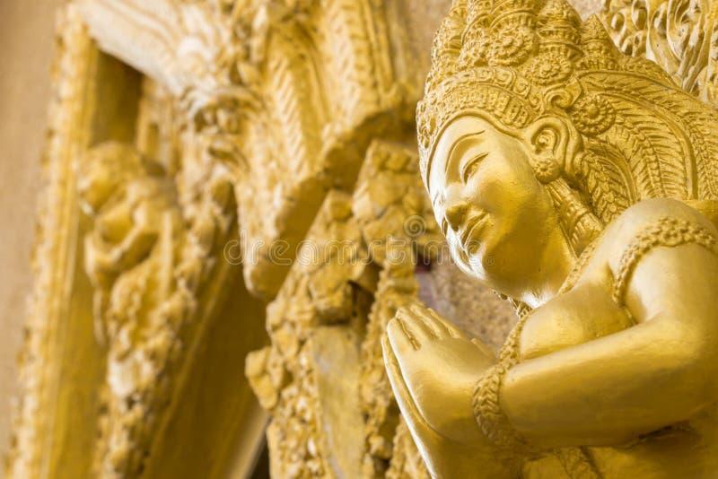 La estatua del oro de las mujeres ruega en templo Ubonratchathani Tailandia fotografía de archivo libre de regalías