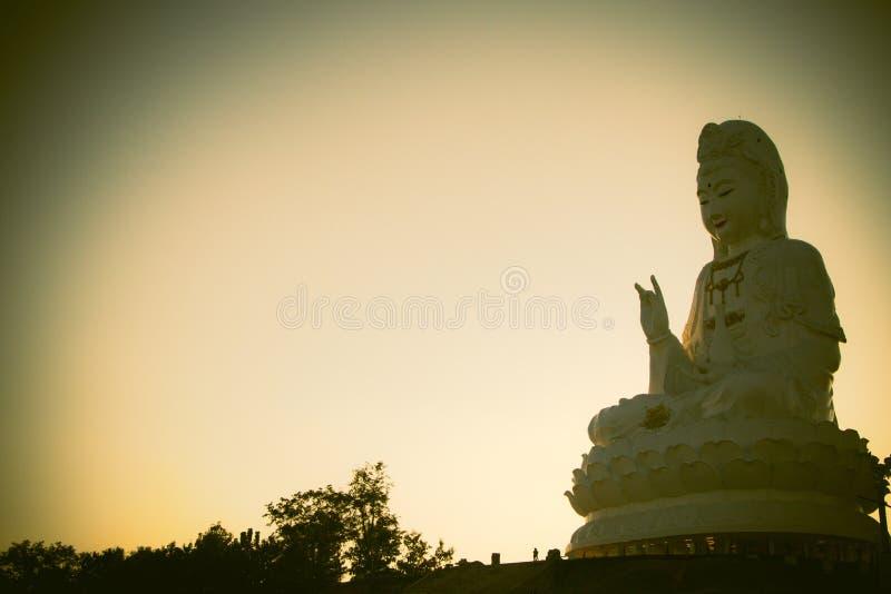 La estatua enorme del yin de Guan en la colina máxima en puesta del sol de la silueta Estatua famosa de Buda del chino foto de archivo