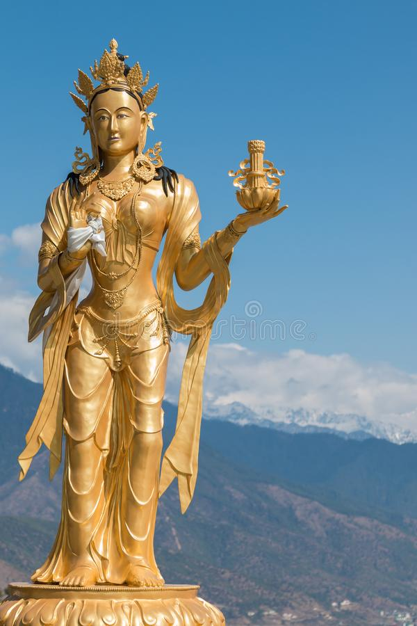 La estatua religiosa femenina en la gran estatua de Buda Dordenma, Timbu, Bhután, con nieve capsuló las montañas en fondo fotografía de archivo