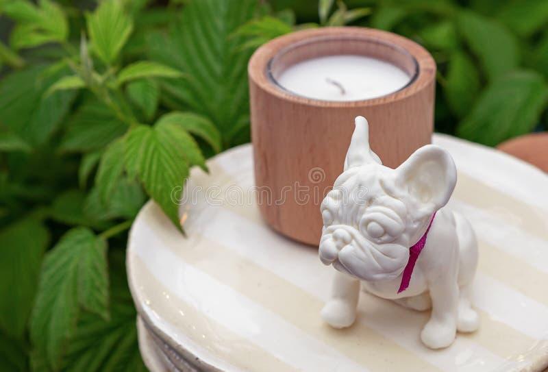 La estatuilla de cerámica de un pequeño dogo francés se coloca en una placa con una vela imagenes de archivo