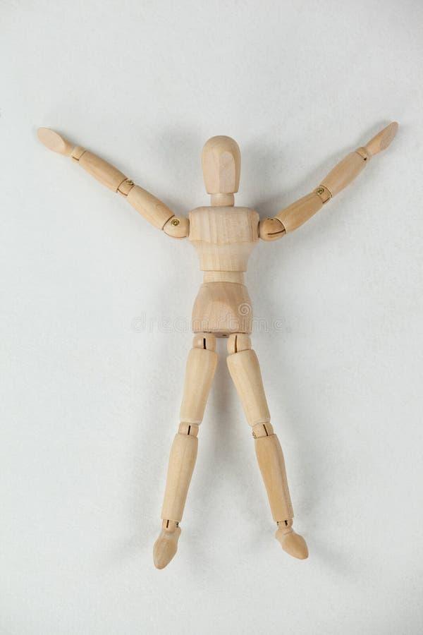 La estatuilla de madera que mentía en piso con los brazos se separó de par en par imagen de archivo