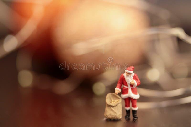 La estatuilla miniatura de Santa Claus con los regalos empaqueta imagen de archivo