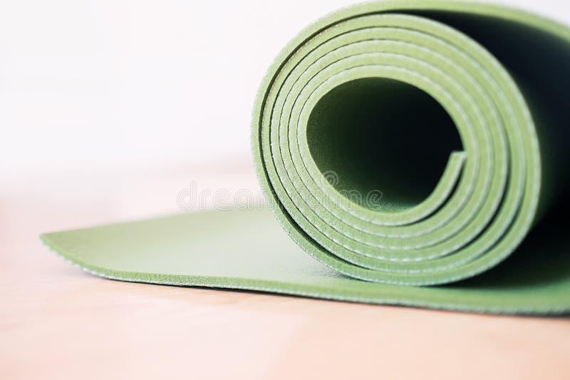 La estera verde de la yoga rodó para arriba después de entrenar fotografía de archivo libre de regalías