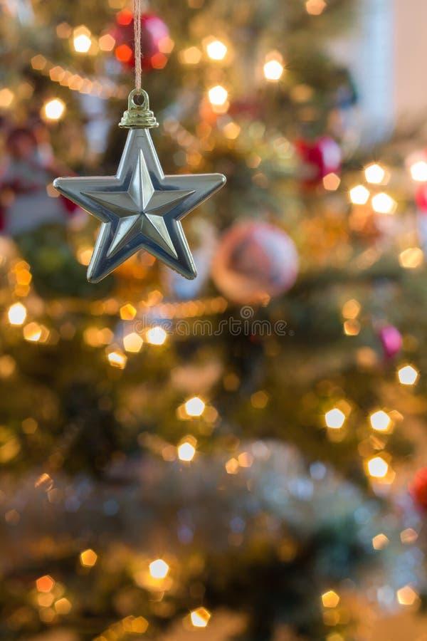 la estrella Cinco-acentuada cuelga delante del árbol de navidad colorido fotografía de archivo libre de regalías