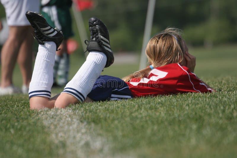 La estrella de fútbol de la muchacha mira el juego fotografía de archivo