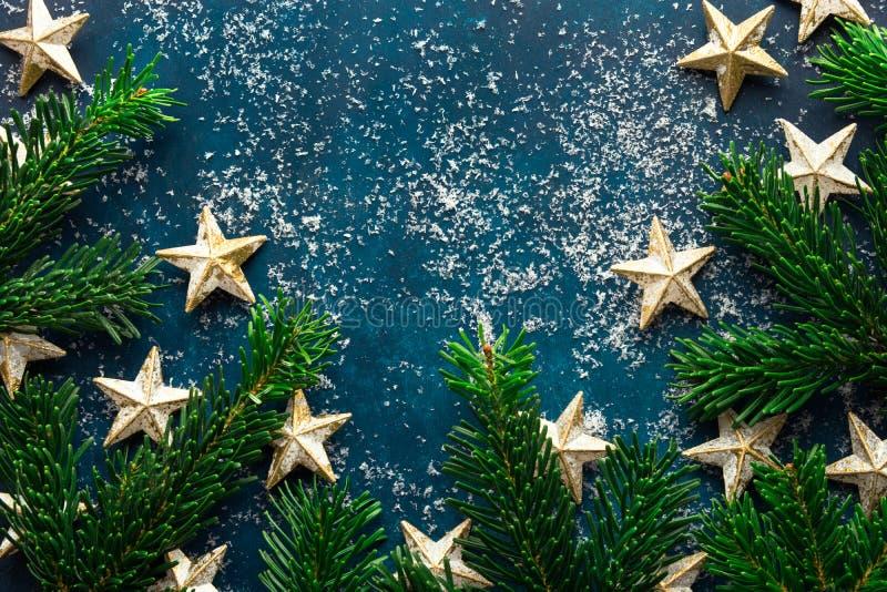 La estrella de oro decorativa mullida fresca de las ramas de árbol de abeto adorna el polvo de la nieve en el contexto azul marin fotografía de archivo libre de regalías