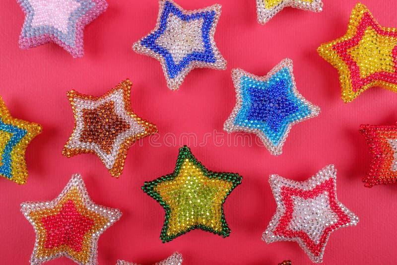 La estrella del Año Nuevo de la Navidad protagoniza diversos colores hechos de las gotas hechas a mano en fondo rosado rojo imagenes de archivo