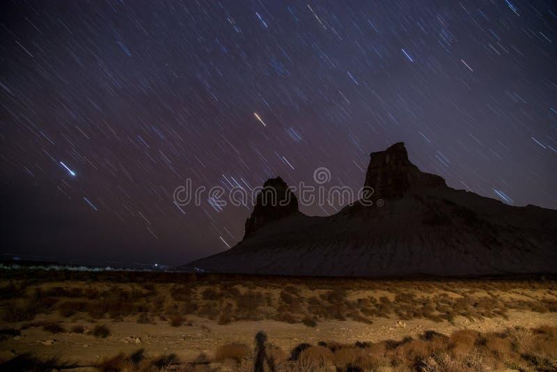 La estrella se arrastra en la noche sobre el barranco de la montaña de Boszhira, Mangistau, desierto de Kazajistán en primavera imagenes de archivo
