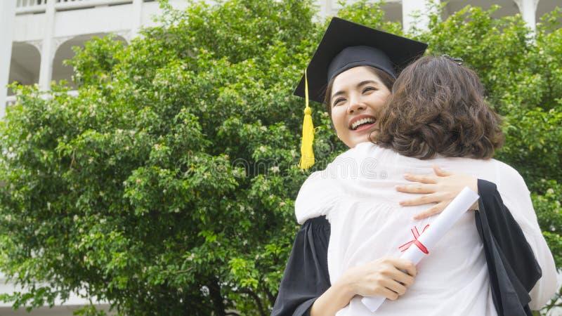 La estudiante con los vestidos de la graduación y el sombrero abrazan al padre adentro imagen de archivo