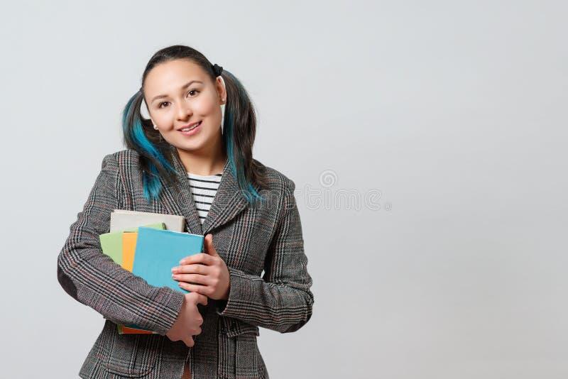 La estudiante con una pila de libros en sus manos mira la cámara y las sonrisas en fondo ligero fotografía de archivo libre de regalías