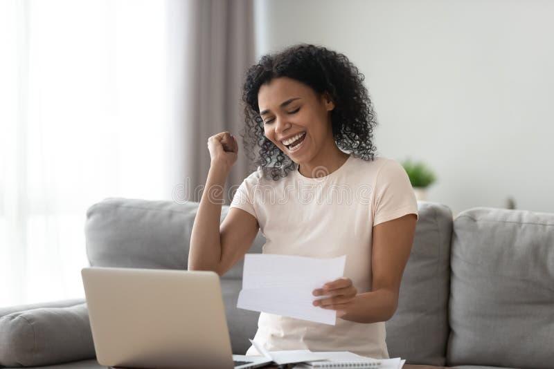La estudiante negra extática emocionada leyó buenas noticias en letra fotos de archivo libres de regalías