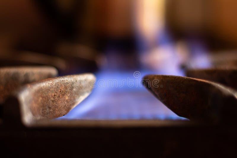 La estufa de gas se giró Acerqúese al protector del metal para apoyar las cacerolas Llama del color azul desenfocado de detrás Ga imágenes de archivo libres de regalías
