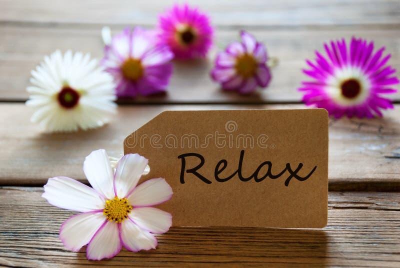 La etiqueta con el texto se relaja con los flores de Cosmea fotos de archivo