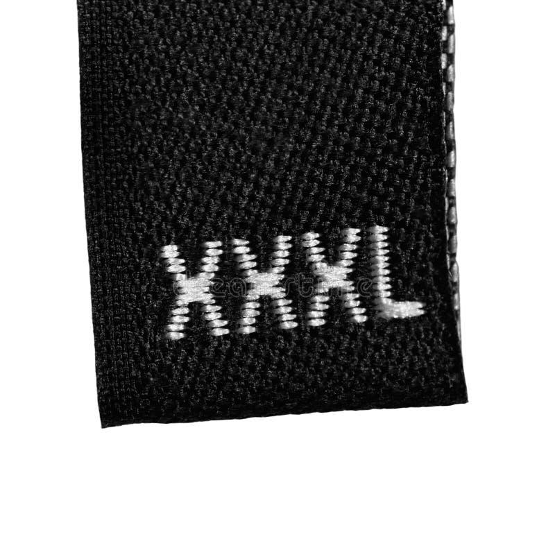 La etiqueta de la escritura de la etiqueta de la ropa de la talla de XXXL, se ennegrece aislado imagen de archivo libre de regalías