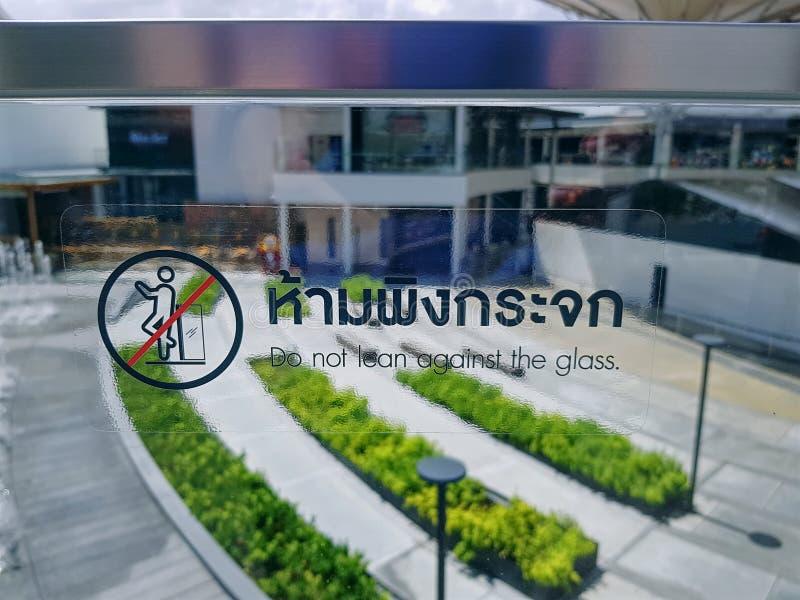 La etiqueta engomada con la muestra y las palabras en tailandés e inglés de hacen no magro contra el vidrio fotografía de archivo libre de regalías