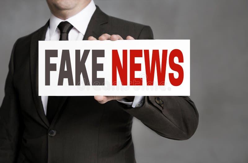 La etiqueta falsa de las noticias es llevada a cabo por el hombre de negocios fotos de archivo