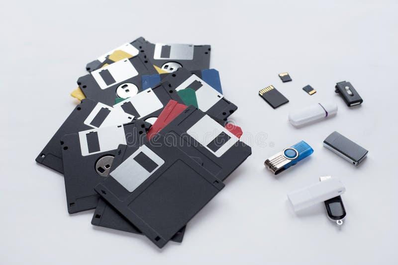 La evolución del dispositivo de almacenamiento de los datos digitales Diskettes, memorias USB y tarjetas de memoria aisladas en e foto de archivo
