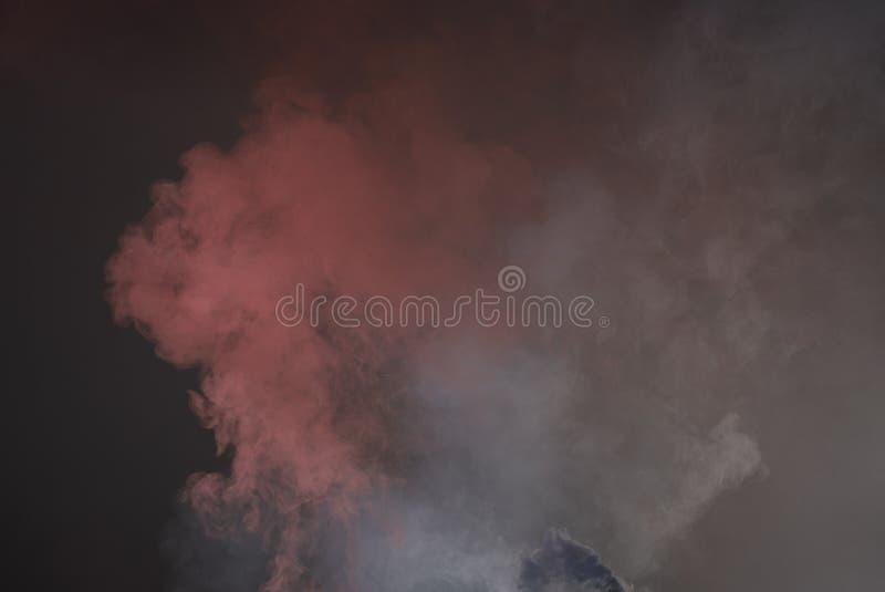 La explosión del polvo coloreado multi La nube del polvo del color que brilla intensamente en fondo negro imagenes de archivo