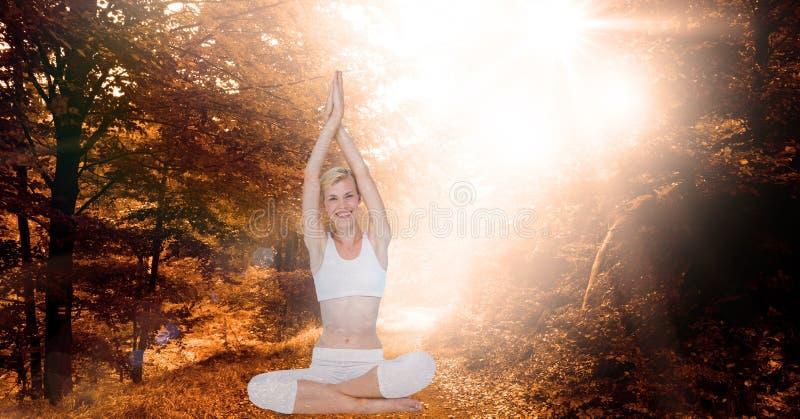 La exposición doble de la mujer con las manos abrochó hacer yoga en bosque fotografía de archivo