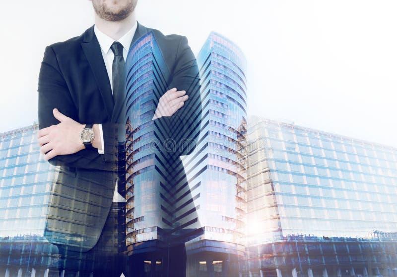 La exposición doble de los edificios del negocio y el hombre de negocios doblaron hola foto de archivo