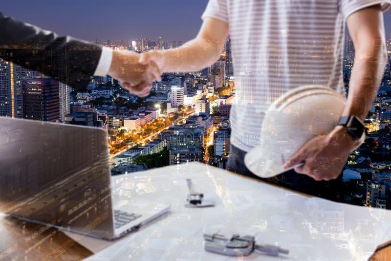 La exposición doble de la mano del hombre de negocios y de la arquitectura que sacude el equipo acertado de las manos trabaja foto de archivo