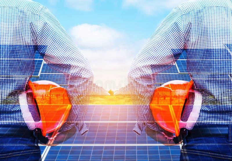 La exposición doble dirige llevar a cabo la estación de la energía solar del frente del casco de seguridad fotografía de archivo