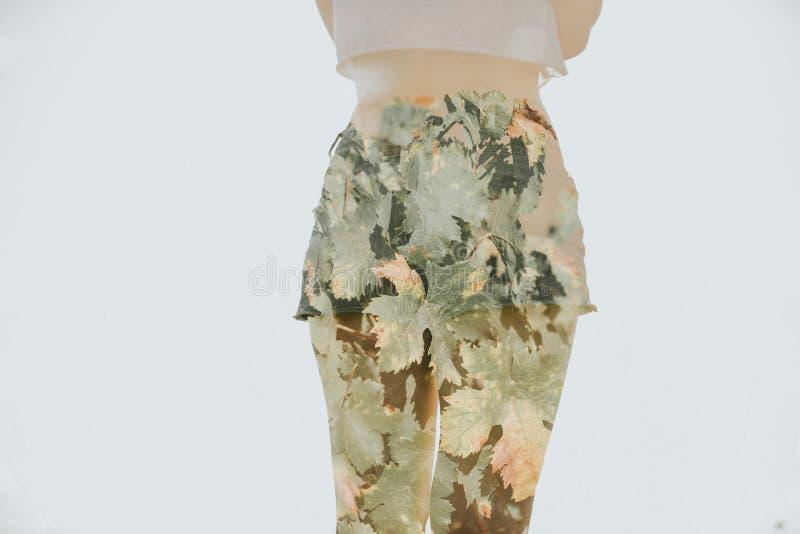 La exposición doble fresca del vago de la mujer en pantalones cortos se mezcló con las hojas de la planta fotografía de archivo