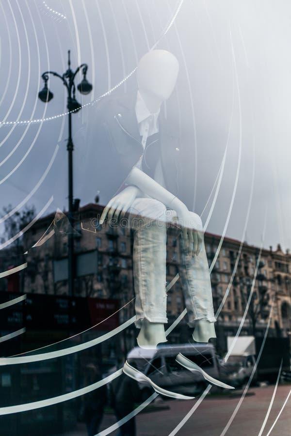 La exposici?n doble es una reflexi?n de la ciudad en la ventana de cristal de la tienda con un maniqu? en ropa de moda imagen de archivo libre de regalías
