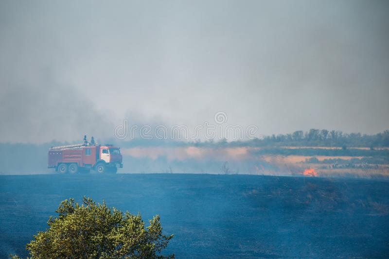 La extinción, el coche de bomberos y los salvadores del bombero extinguen los incendios forestales o incendio fuera de control imagen de archivo