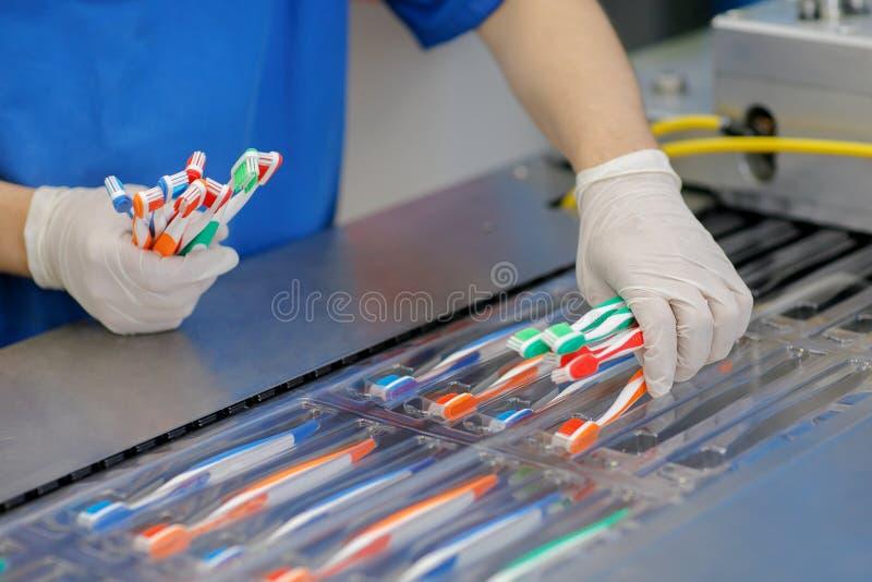 La fábrica produce y empaqueta los cepillos de dientes de diversos colores foto de archivo