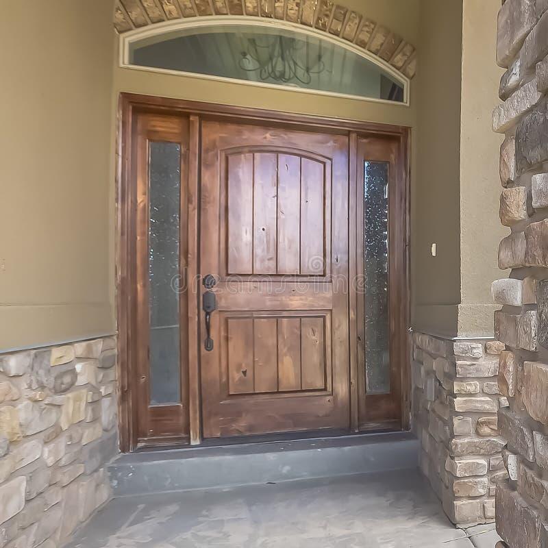 La façade à la maison de cadre carré avec la porte en bois brune a givré les feux de position et la fenêtre de traverse arquée photo stock