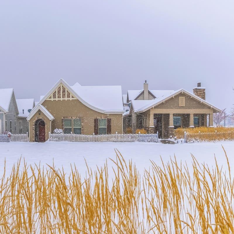 La façade à la maison de place avec les toits neigeux et entourée par la neige a couvert la terre en hiver image libre de droits