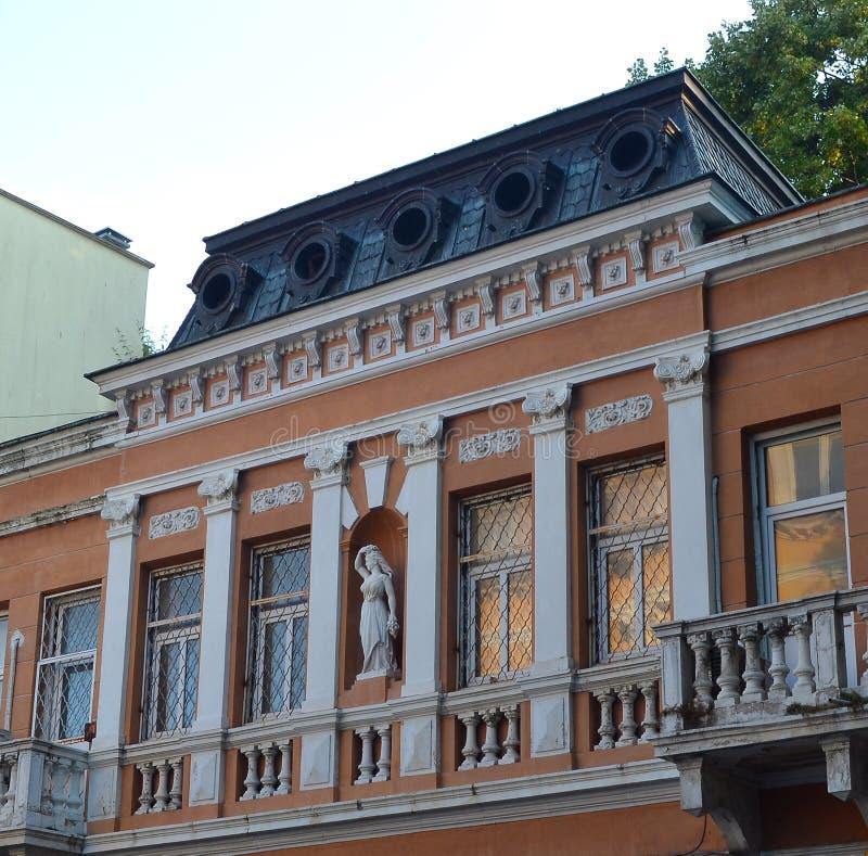 La façade du vieux bâtiment est décorée d'une statue d'une femme et des moitié-colonnes image stock