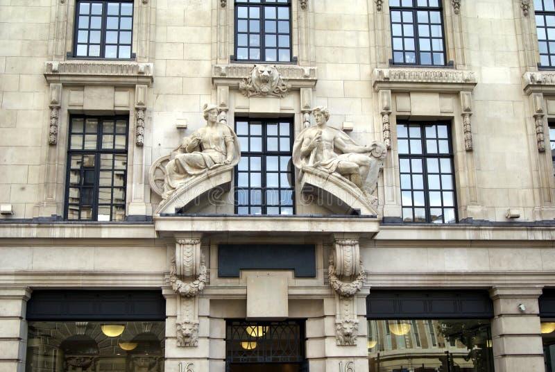 La façade fleurie avec l'homme et les statues et le lion de femme dirige des sculptures photographie stock libre de droits