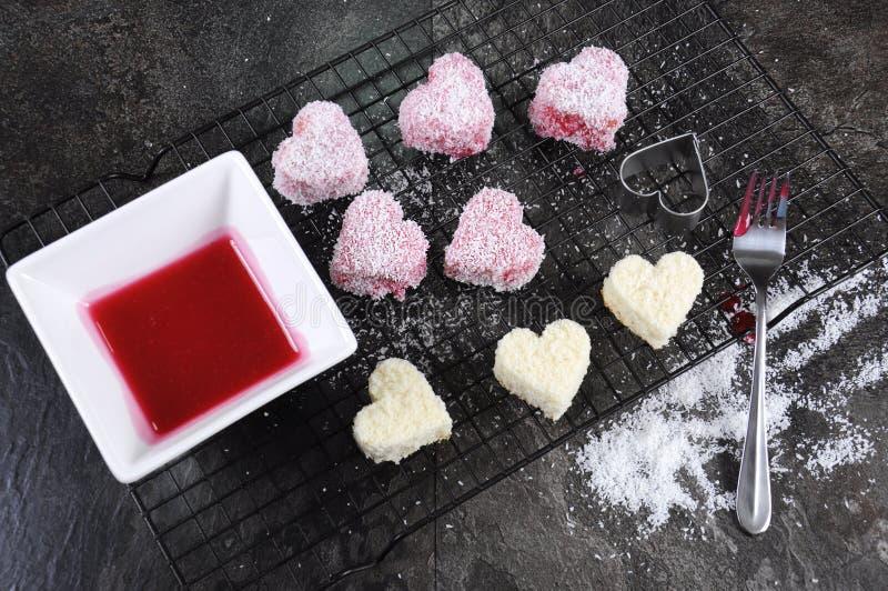 La fabbricazione del cuore australiano di rosa di stile modellare il piccolo lamington agglutina immagine stock libera da diritti