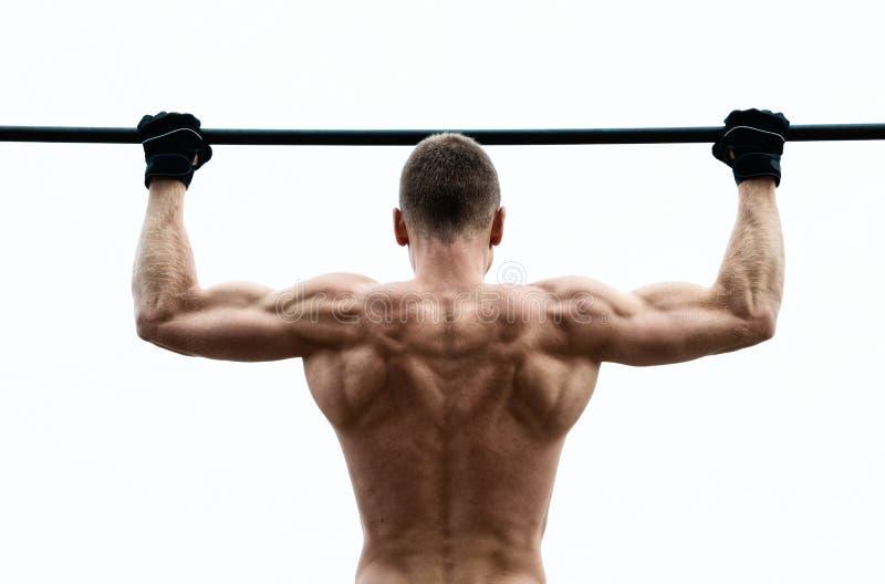 La fabbricazione dell'uomo del muscolo tira su sulla barra orizzontale contro il cielo fotografia stock