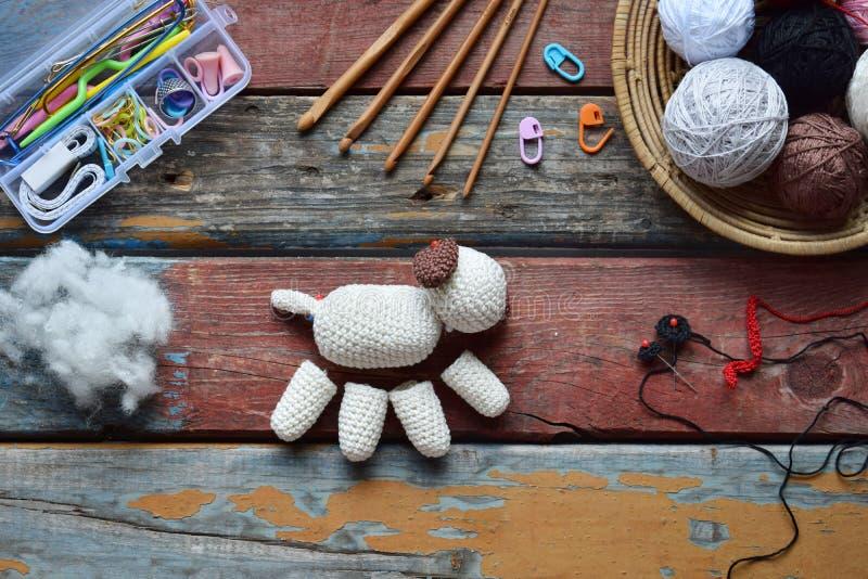 La fabbricazione lavora all'uncinetto il cane bianco Giocattolo per i bambini o il ninnolo Sulla tavola infila, aghi, il gancio,  fotografie stock libere da diritti