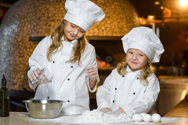 La fabricación de la pasta para la pizza es diversión - pequeños cocineros imágenes de archivo libres de regalías