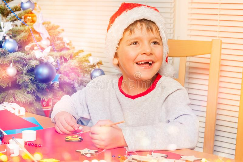 La fabricación linda del muchacho posee los ornamentos de la Navidad en casa foto de archivo libre de regalías