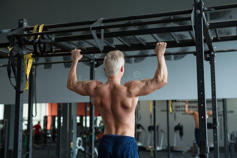 La fabricación muscular del hombre del atleta levanta en gimnasio Entrenamiento del culturista en el club de fitness que muestra  imágenes de archivo libres de regalías