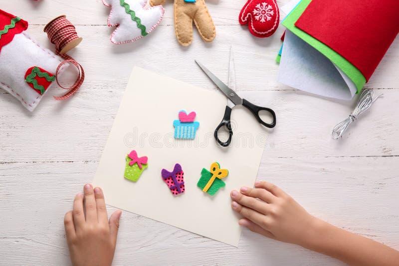 La fabrication d'enfant a senti des jouets de Noël à la table en bois photographie stock