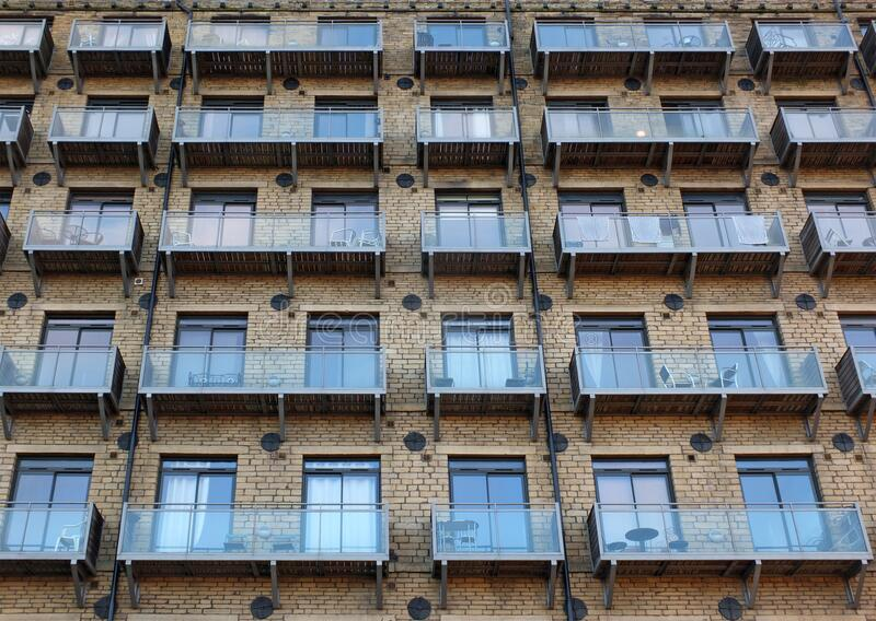 La facciata di un grande vecchio edificio in pietra trasformato in appartamenti con moderni balconi di vetro fotografie stock libere da diritti
