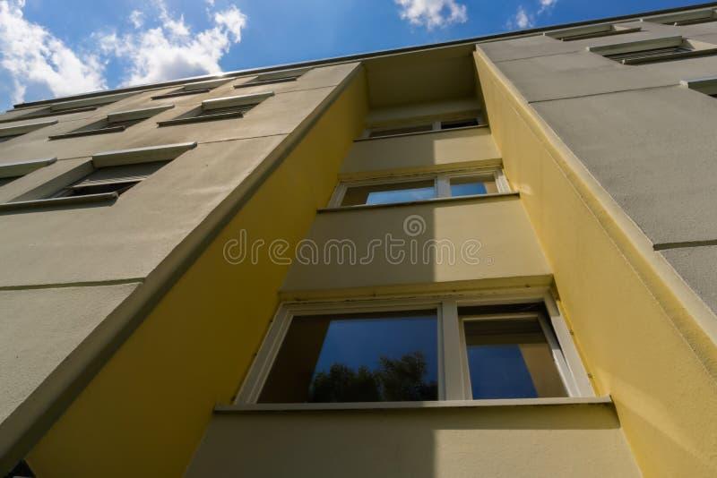 La facciata frontale superiore di una costruzione sotto un cielo blu e nuvoloso immagine stock libera da diritti