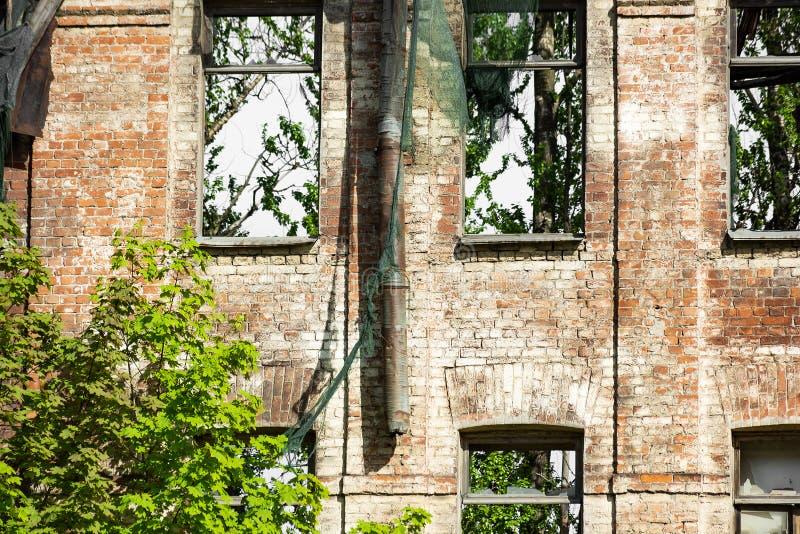 La fachada abandonó el edificio de ladrillo demasiado grande para su edad con la hierba y los árboles imagen de archivo